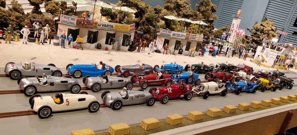 Coppa D'Oro field featuring 22 vintage slot cars with the pit lane in the background