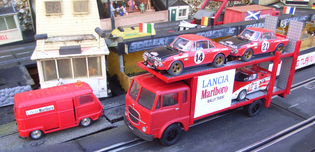 Red Lancia car transporter with three cars loaded