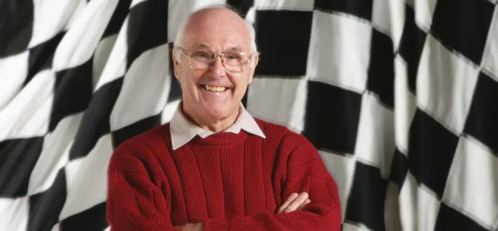A smiling Murray Walker, standing in front of a chequered flag